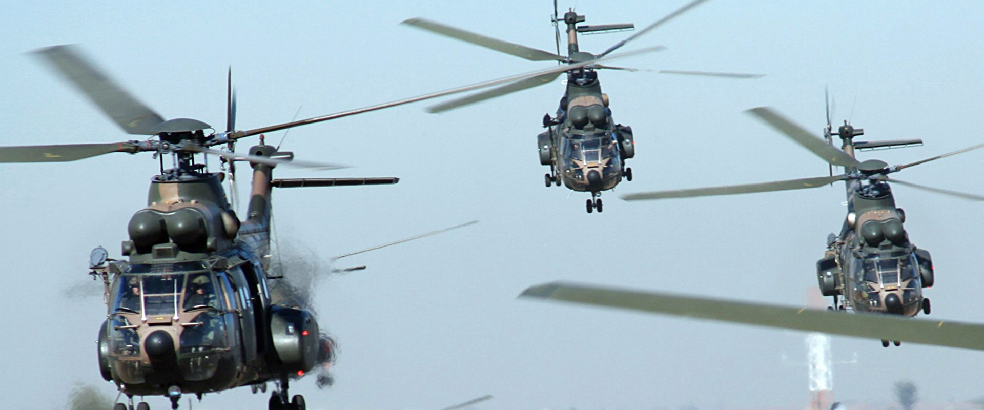 Fleet of helicopters taking to the skies over a runway